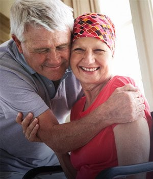 Smiling cancer patient being hugged by a relative. Chronic medical conditions.
